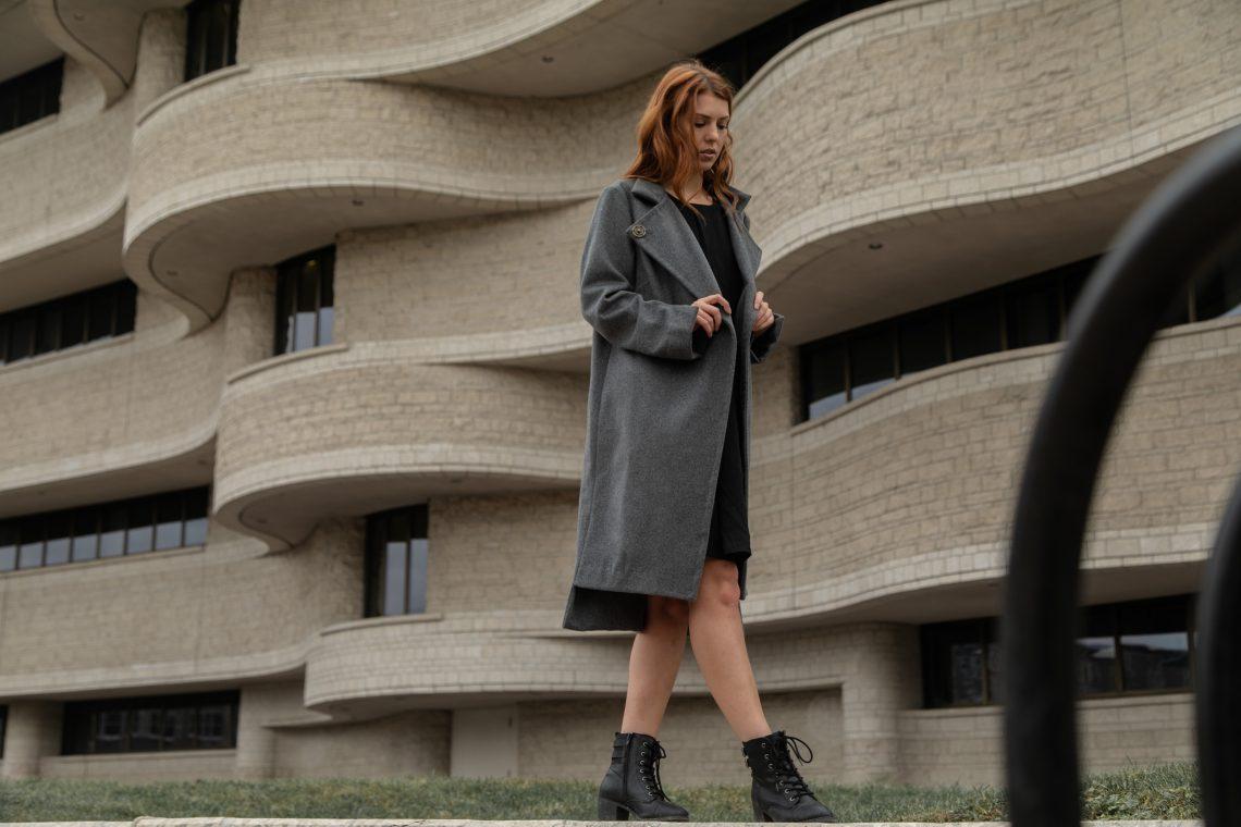 woman wearing coat walking near brown building