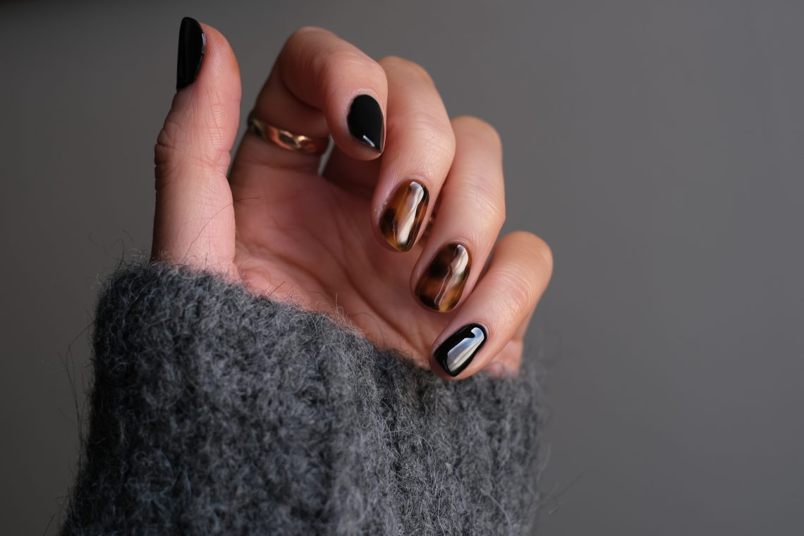 person wearing silver ring with black manicure