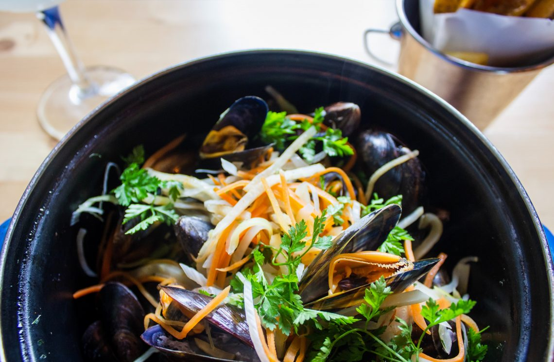 shallow focus photo of mussel dish on black pot